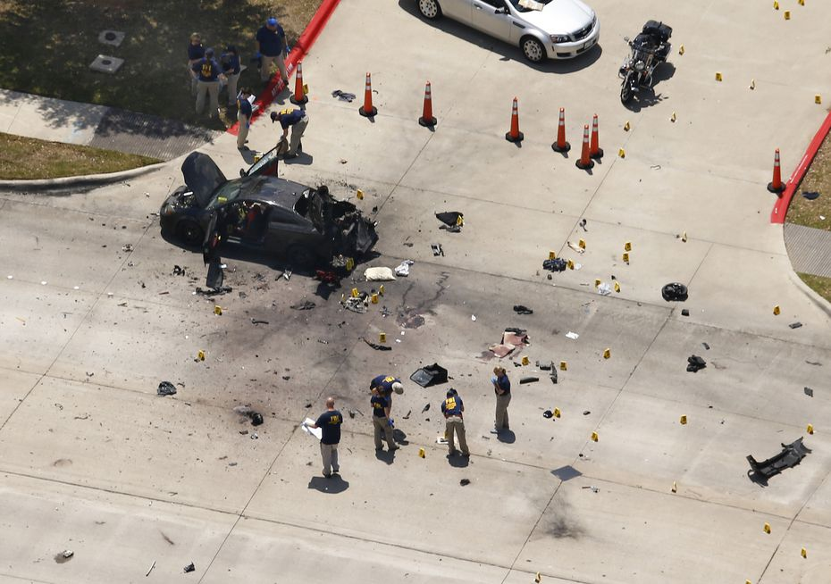 Investigators work near the car of the assailants who shot a security guard at the Curtis Culwell Center Sunday, after the SWAT team detonated the car in case it had any explosives in Garland.