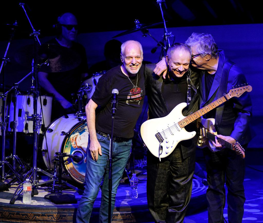 Steve Miller, right, of the Steve Miller Band, gives his long time friend Jimmie Vaughan, center, a hug after they performed several songs with Peter Frampton (left) during the Steve Miller Band concert at Austin City Limits at the Moody Theater, in Austin, Texas, July 30, 2018.