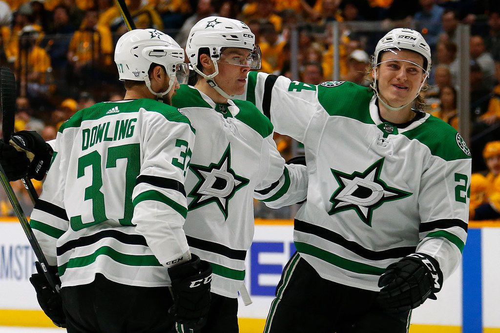 Roope Hintz (24) and Justin Dowling (37) of the Stars congratulate teammate Miro Heiskanen (4) on scoring a goal against the Predators during the second period in Game 1 of the Western Conference first round in the 2019 NHL Stanley Cup Playoffs at Bridgestone Arena on April 10, 2019, in Nashville, Tenn.