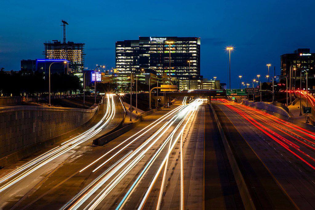 A long exposure shows traffic on the Dallas North Tollway at Tennyson Parkway with Legacy West, Liberty Mutual and The Shops at Legacy seen at top on July 13, 2018, in Plano.