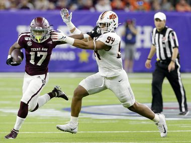 Texas A&M wide receiver Ainias Smith (17) fends off Oklahoma State defensive end Trace Ford (94) during the first half of the Texas Bowl NCAA college football game Friday, Dec. 27, 2019, in Houston.