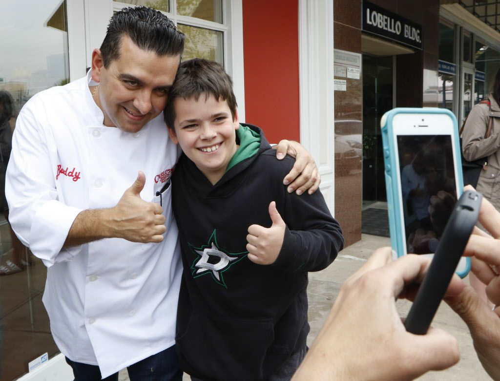 Buddy Valastro, left, took time out his busy day to pose with Harrison Gullatt, 10, at Carlo's Bake Shop on Friday.