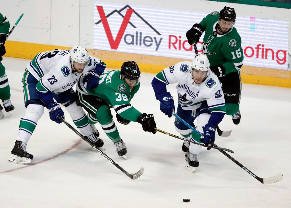 Vancouver Canucks defenseman Alexander Edler (23) and center Bo Horvat (53) work to keep the puck away from Dallas Stars right wing Joel L'Esperance (38) and center Jason Dickinson (16) during the third period of an NHL hockey game in Dallas, Sunday, March 17, 2019. (AP Photo/Tony Gutierrez)