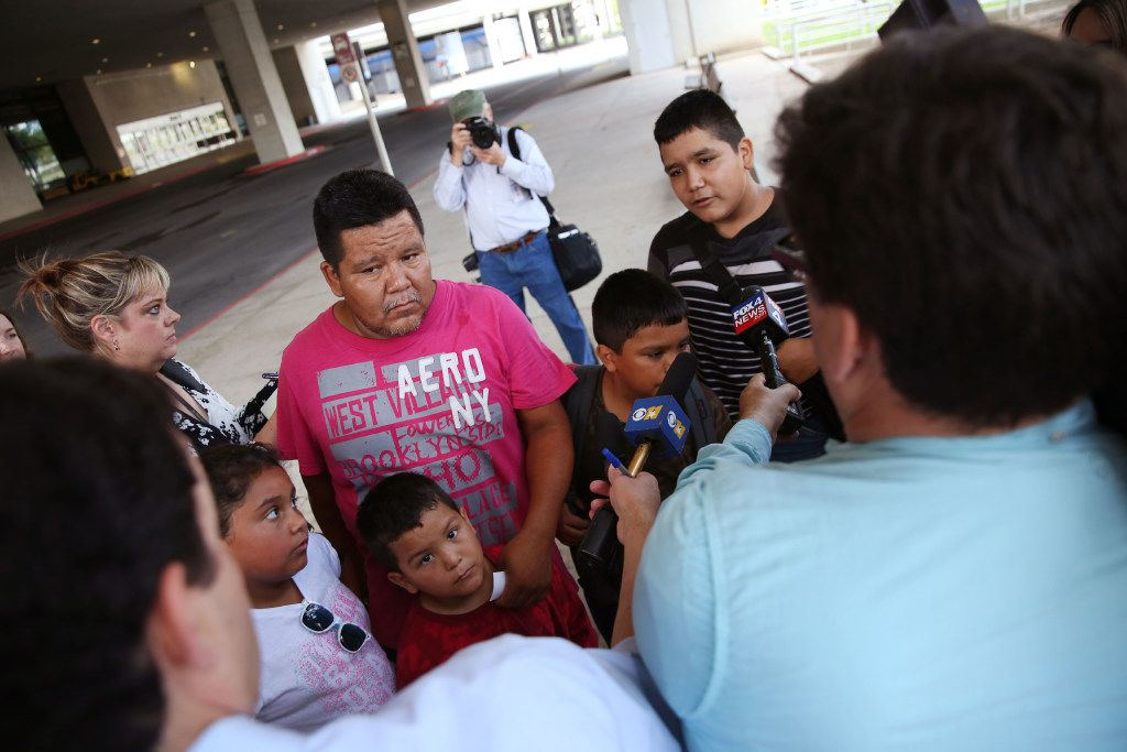 """Luis Banda (far right), 12, an evacuee from Dickinson, Texas speaks to the media alongside his family after arriving at the """"mega shelter"""" outside the Kay Bailey Hutchison Convention Center in Dallas on Tuesday, Aug. 29, 2017."""