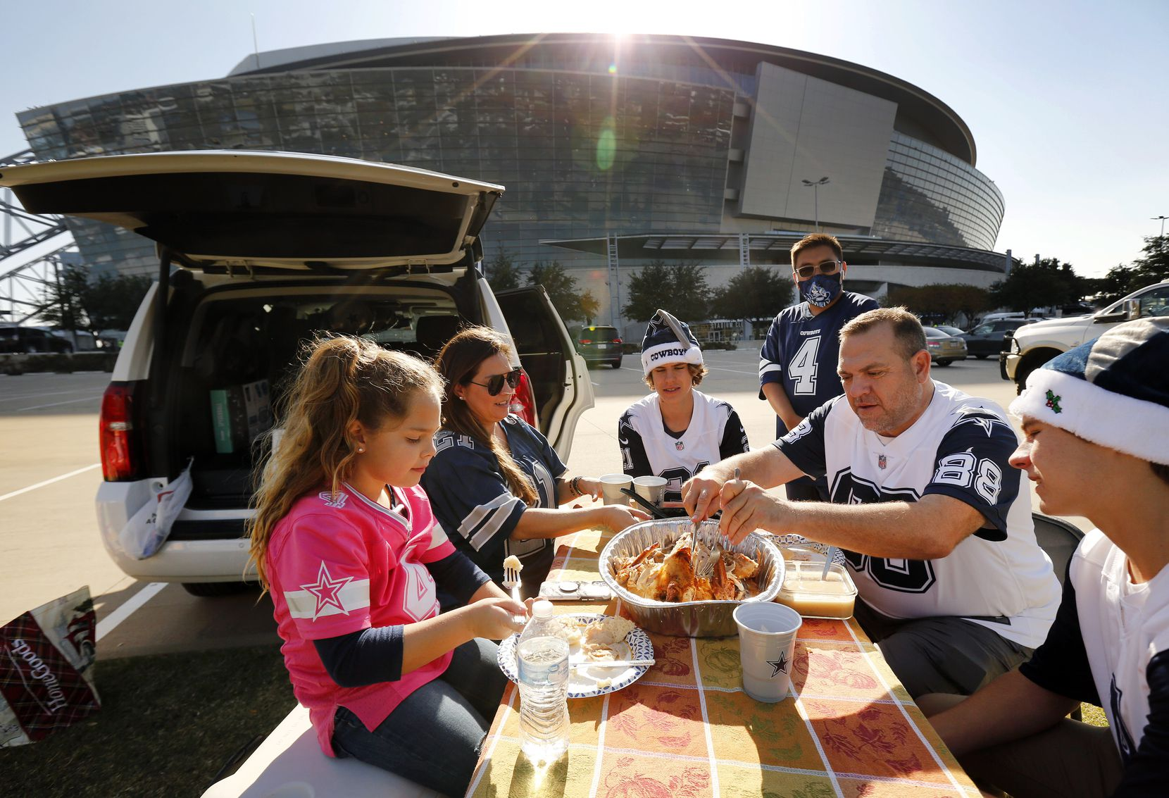 Dallas Cowboys fans from Newport Beach, California dine on a Cajun Thanksgiving Day turkey as they tailgate outside AT&T Stadium in Arlington, Thursday, November 26, 2020. The Carson family from left, Grace, mom Christa, Cade, cousin William Hagermann, dad Todd and Cole drove to see their team play the Washington Football Team. (Tom Fox/The Dallas Morning News)