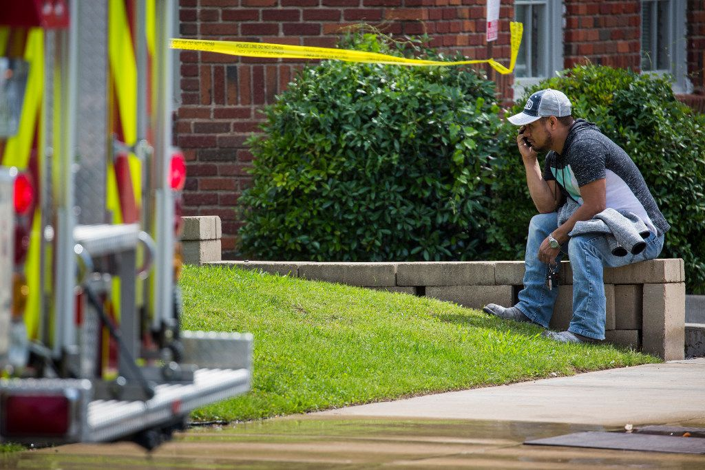A man watches as Dallas Fire-Rescue responds to a scene at 1700 Arts Plaza (near Ross Ave. and Flora Street) where a crane accident resulted in a fatality on Monday, April 24, 2017, in Dallas.  One person was killed, one was transported to the hospital with injuries that were not life-threatening and one person was treated and released at the scene. (Smiley N. Pool/The Dallas Morning News)