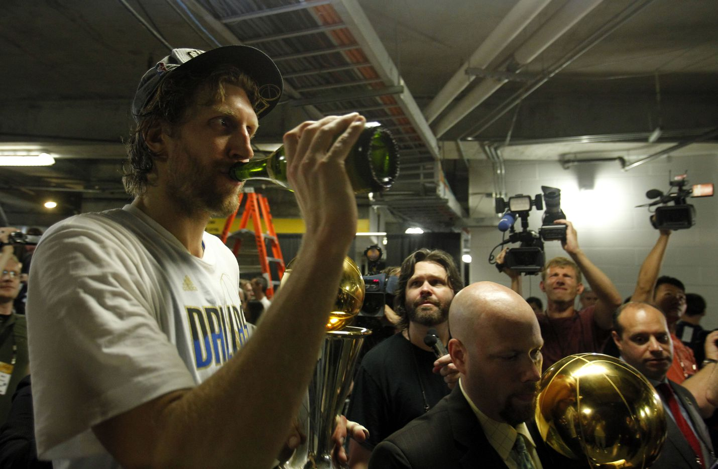 Dallas Mavericks power forward Dirk Nowitzki (41) drinks champagne as he is escorted to another interview after winning in game six of the NBA Finals between the Miami Heat and the Dallas Mavericks at the American Airlines Arena in Miami, Florida, June 12, 2011. The Mavericks won 105-95 to take the title. (Vernon Bryant/The Dallas Morning News)