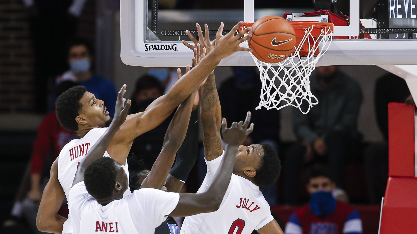 (L to R) SMU forwards Feron Hunt, Yor Anei (10) and guard Tyson Jolly (0) vie for a rebound during the second half of a college basketball game against Memphis in Dallas, Thursday, January 28, 2021. SMU won 67-65.