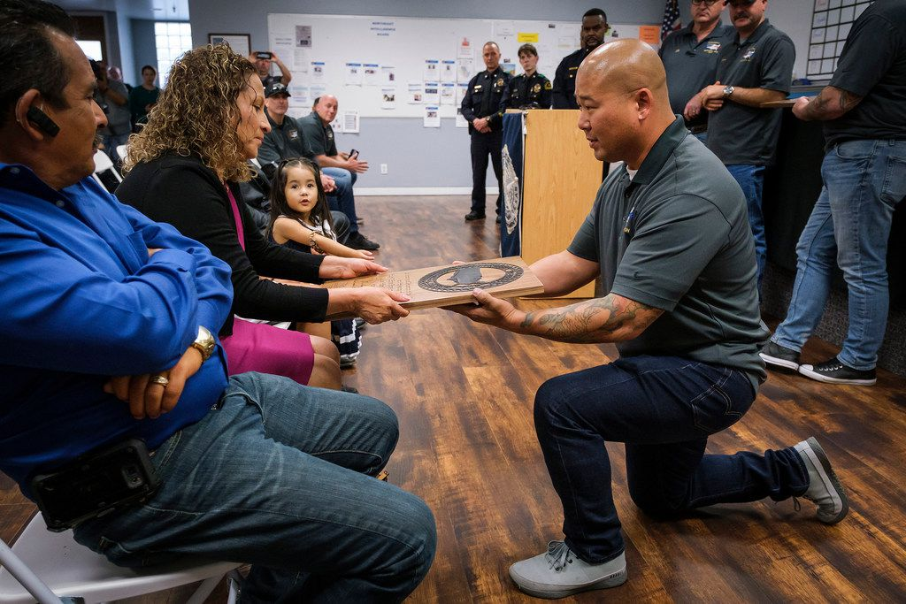 Sergeant Aram Choe of the El Monte, Calif., police department presents a plaque from the Cannonball Memorial Run to Julia Santander, the mother of slain Dallas officer Rogelio Santander, Jr., during a ceremony at the Dallas Police Northeast Patrol Division on Friday, April 12, 2019, in Dallas.
