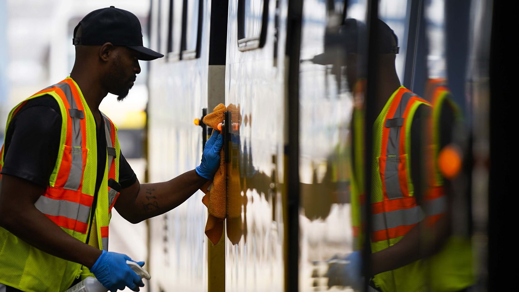 Michael Beck limpia uno de los vagones de un tren de DART con desinfectante. DART está tomando varias medidas, incluido el cierre de centros de tránsito, para prevenit la propagación del coronavirus.=