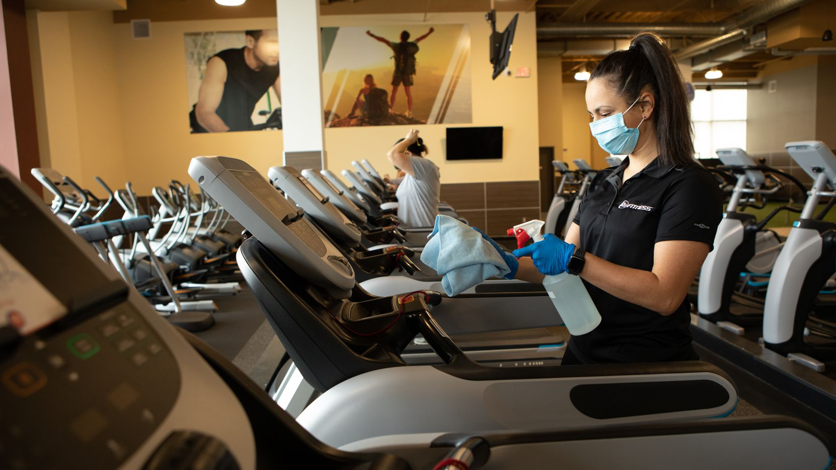 An employee sanitizes treadmills at a 24 Hour Fitness location. The company recently announced it was permanently closing 24 club locations across Texas as it repositioned itself amid the pandemic.