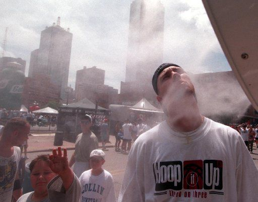 ORG XMIT:  [NS_21Hoop3]  Caption: 6/21/97---Anthony Salisbury, right, of Ft. Worth, cools  his face in front of a cool mist machine after his team ' The Hoop Troop' finished a game at the Hoop-it-Up 3 on 3 basketball  tourney in the West End Saturday in downtown Dallas.  Photographer: THOMPSON, Irwin Credit: 104876  Date: 19970621  ObjectName: NS_21Hoop3  Source: Sports