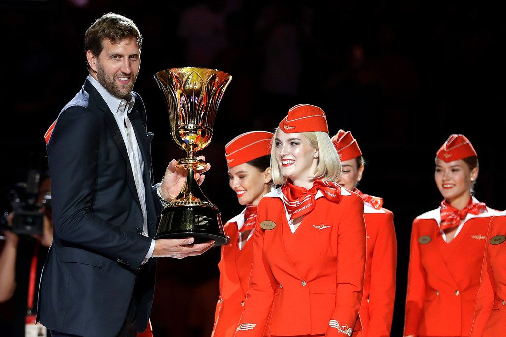 NBA basketball player Dirk Nowitzki holds the James Naismith Trophy, awarded to the FIBA Basketball World Cup champions, during their group phase basketball game between China and Ivory Coast in the FIBA Basketball World Cup at the Cadillac Arena in Beijing, Saturday, Aug. 31, 2019. (AP Photo/Mark Schiefelbein)