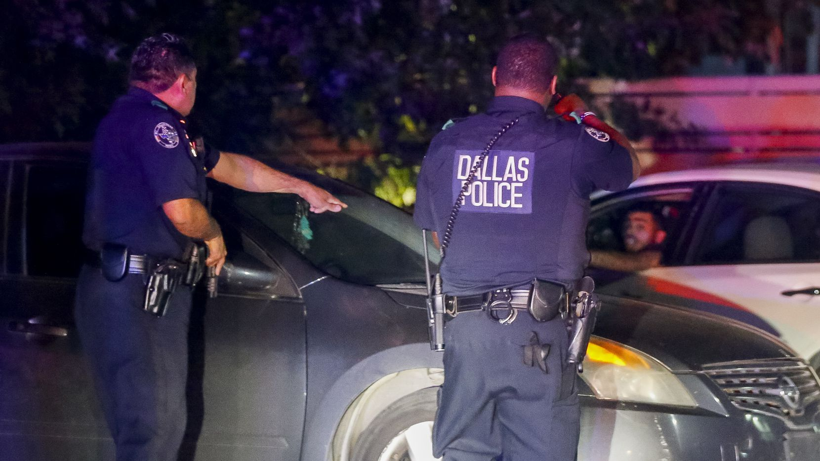 Dallas Police Deputy Chief Israel Herrera (left) and another officer give commands to the driver of a vehicle during a felony traffic stop on Friday, Sept. 24, 2021, in Dallas. Herrera was on patrol in downtown when he witnessed gunshots fired from a vehicle, he then followed the vehicle until more officers arrived and were able to assist. (Elias Valverde II/The Dallas Morning News)