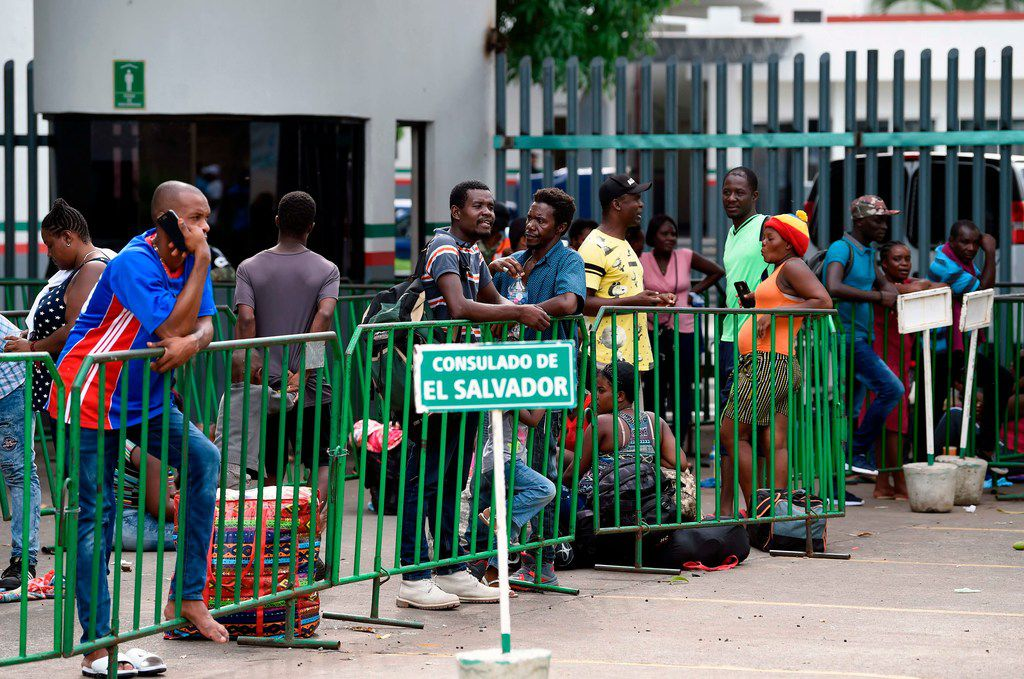 Migrants from different nationalities queue outside the Mexican National Institute of Migration, near a sign marking the line for the Salvadorean consulate, in Tapachula, Chiapas State, Mexico, on June 20, 2019.
