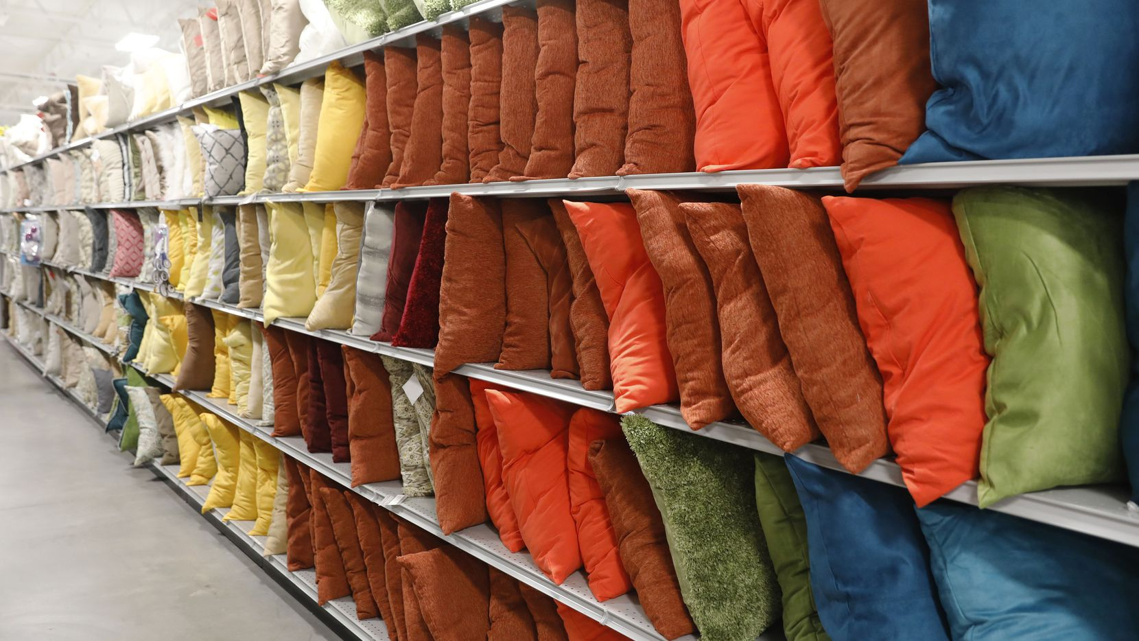 Accent pillows line the shelves in At Home,