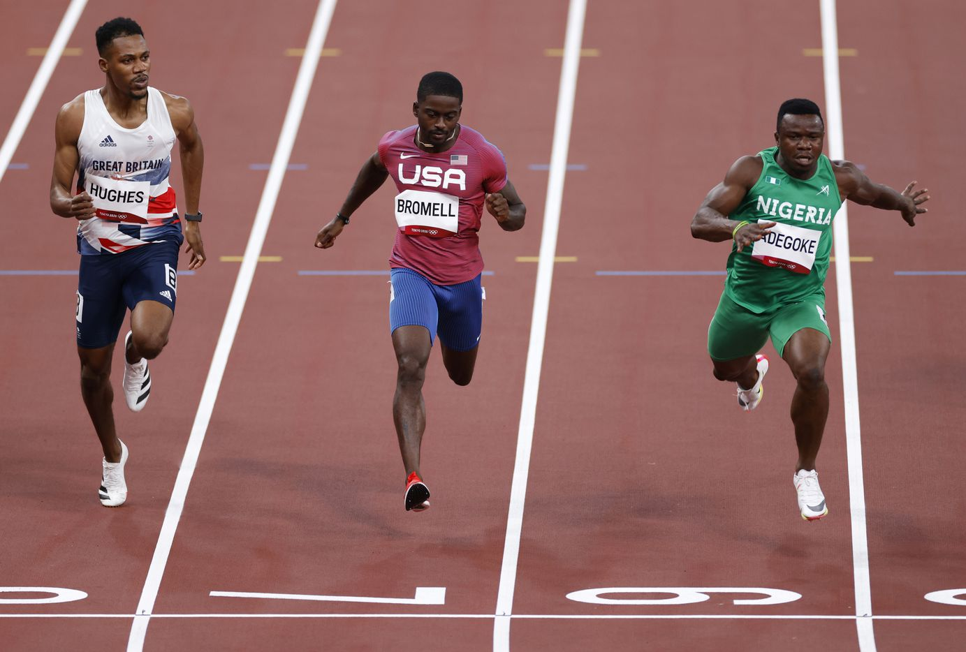 Great Britain's Zharnel Hughes, USA's Trayvon Bromell, and Nigeria's Enoch Adegoke race to the finish in the 100 meter qualifying race during the postponed 2020 Tokyo Olympics at Olympic Stadium, on Saturday, July 31, 2021, in Tokyo, Japan. Bromell finished fourth with a time of 10.04. (Vernon Bryant/The Dallas Morning News)