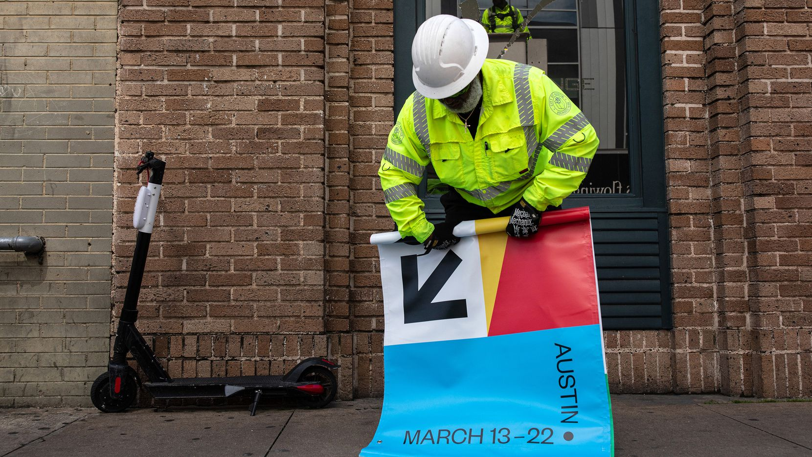 Joseph Alberts rolls up a South by Southwest banner after it was removed from a lamp post in downtown Austin.
