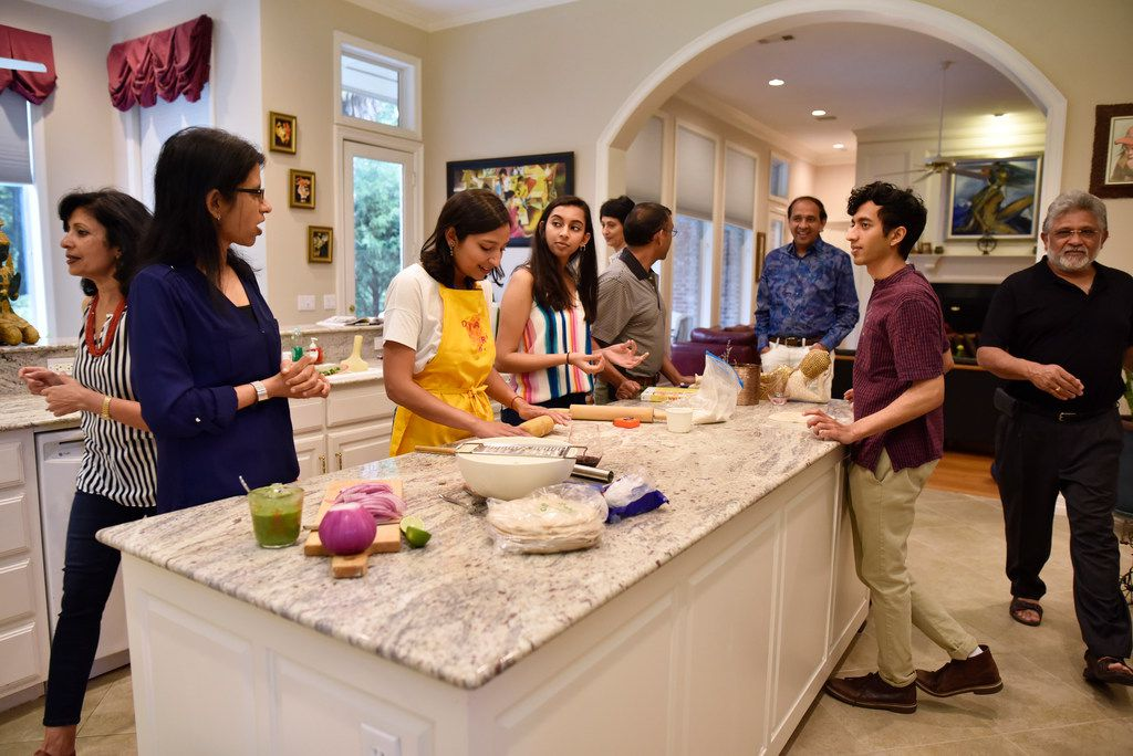 Food writer Priya Krishna, in the yellow apron, speaks to her family while preparing roti and paratha.