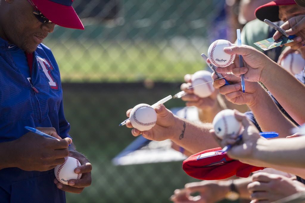 Texas Rangers third baseman Adrian Beltre signs autographs for fans during a spring training workout at the team's training facility on Sunday, Feb. 28, 2016, in Surprise, Ariz. (Smiley N. Pool/The Dallas Morning News)
