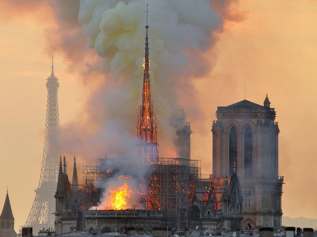 With the Eiffel Tower in the distance, flames and smoke rise from the blaze at Notre Dame Cathedral in Paris that destroyed its spire and its roof but spared its twin medieval bell towers, and prompted a frantic rescue effort to save its most precious artifacts.