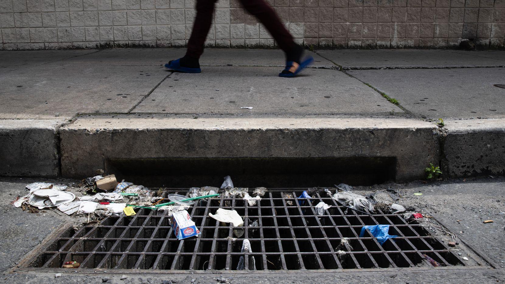 En esta foto del 25 de mayo de 2020, un transeúnte pasa junto a un desagüe con guantes y otros desechos en Filadelfia. Los desechos de la pandemia agravan un problema conocido al taponar alcantarillas y cañerías.