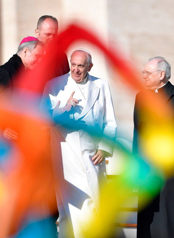 Pope Francis is pictured through colorful scarves waved by faithful at the end of a weekly general audience in St Peter's Square on Wednesday in Vatican City.
