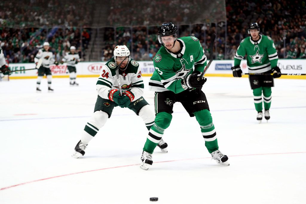 DALLAS, TEXAS - OCTOBER 29:  John Klingberg #3 of the Dallas Stars skates the puck against Matt Dumba #24 of the Minnesota Wild in the second period at American Airlines Center on October 29, 2019 in Dallas, Texas. (Photo by Ronald Martinez/Getty Images)