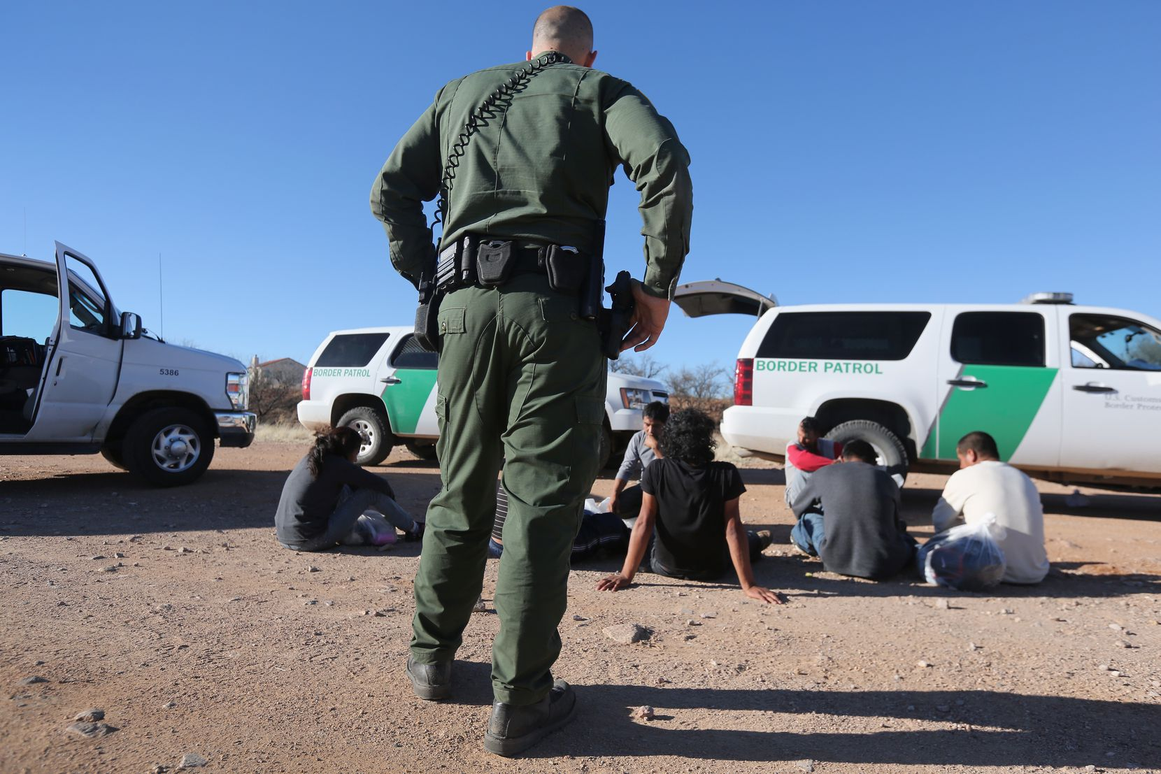 A Border Patrol agent detains suspected unauthorized immigrants in the area of Walker Canyon in Arizona.