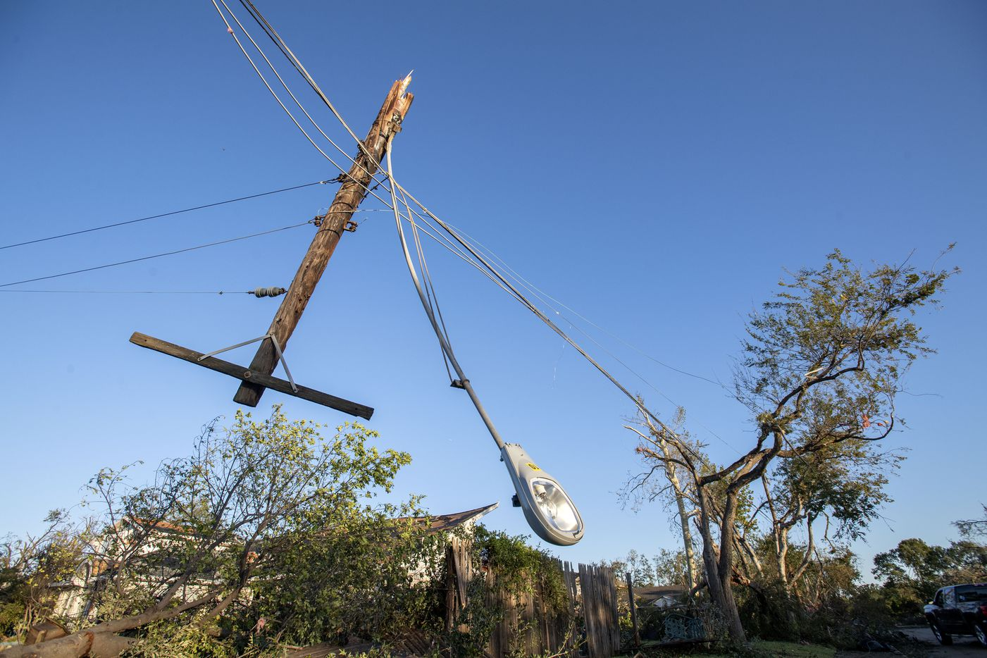 A broken utility pole hangs upside down on Coppedge Lane north of Walnut Hill after Sunday night's tornado on Monday, Oct. 21, 2019 in Dallas.