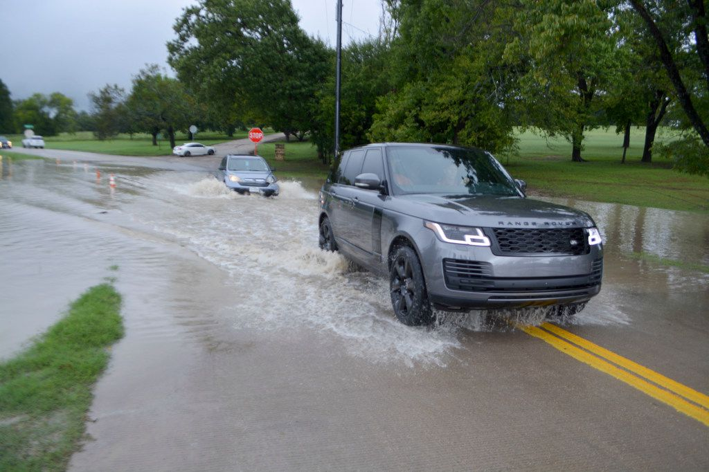 A Range Rover and a car drive through waters flooding out of the banks of White Rock Creek onto Goforth Road.