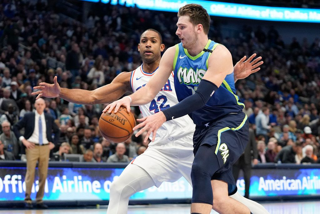 Dallas Mavericks guard Luka Doncic (77) wraps a pass around Philadelphia 76ers center Al Horford (42) during the second half of an NBA basketball game at American Airlines Center on Saturday, Jan. 11, 2020, in Dallas.