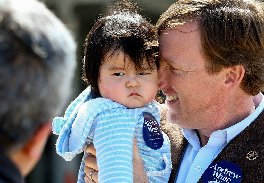 Gubernatorial candidate Andrew White holds 6-month-old Max while talking to Max's father, Peter Kim, outside the West Gray Recreation Center in Houston on March 6, 2018. (Godofredo A. Vasquez /Houston Chronicle via AP)