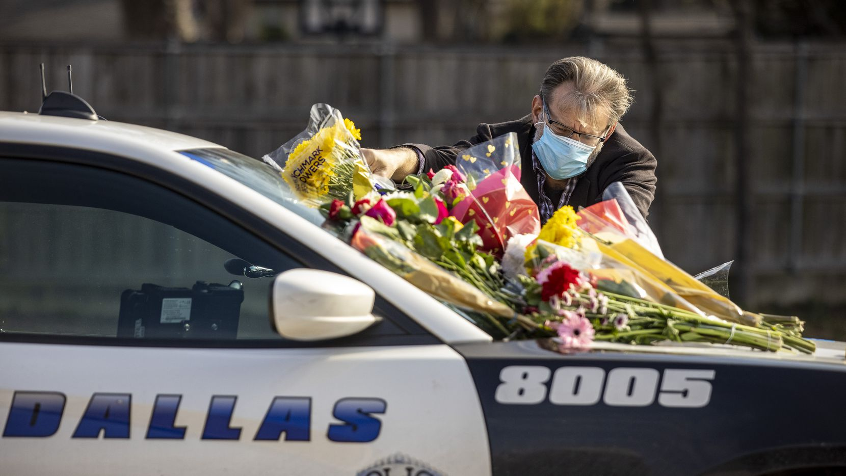 Steve Martindale pays his respects to fallen Dallas Police officer Mitchell Penton at the DPD Northeast Patrol Division building on Saturday, Feb. 13, 2021, in Dallas. Officials say Penton was struck by an intoxicated driver around 1:45 a.m. on Saturday when Penton was working a crash scene in the northbound lanes of the North Central Expressway at Walnut Hill Lane. (Lynda M. González/The Dallas Morning News)