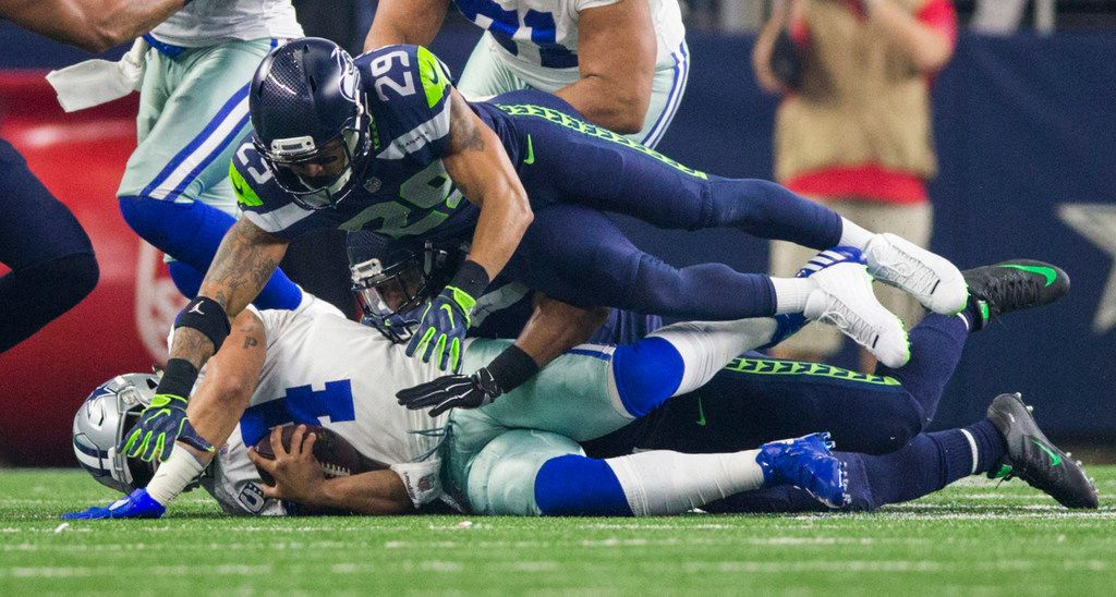 Dallas Cowboys quarterback Dak Prescott (4) is sacked by Seattle Seahawks free safety Earl Thomas (29) during the first quarter of a Christmas Eve NFL game between the Dallas Cowboys and the Seattle Seahawks on Sunday, December 24, 2017 at AT&T Stadium in Arlington, Texas. (Ashley Landis/The Dallas Morning News)