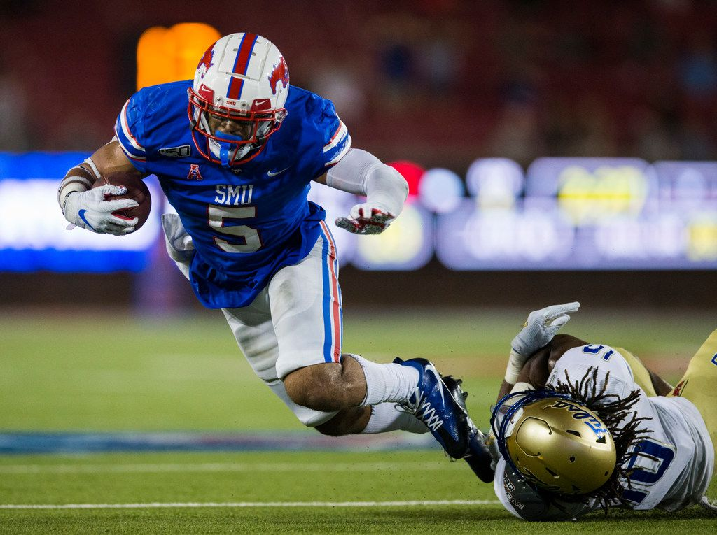 SMU Mustangs running back Xavier Jones (5) is tackled by Tulsa Golden Hurricane safety Manny Bunch (10) during the fourth quarter of an NCAA football game between Tulsa and SMU on Saturday, October 5, 2019 at Ford Stadium on the SMU campus in Dallas. (Ashley Landis/The Dallas Morning News)