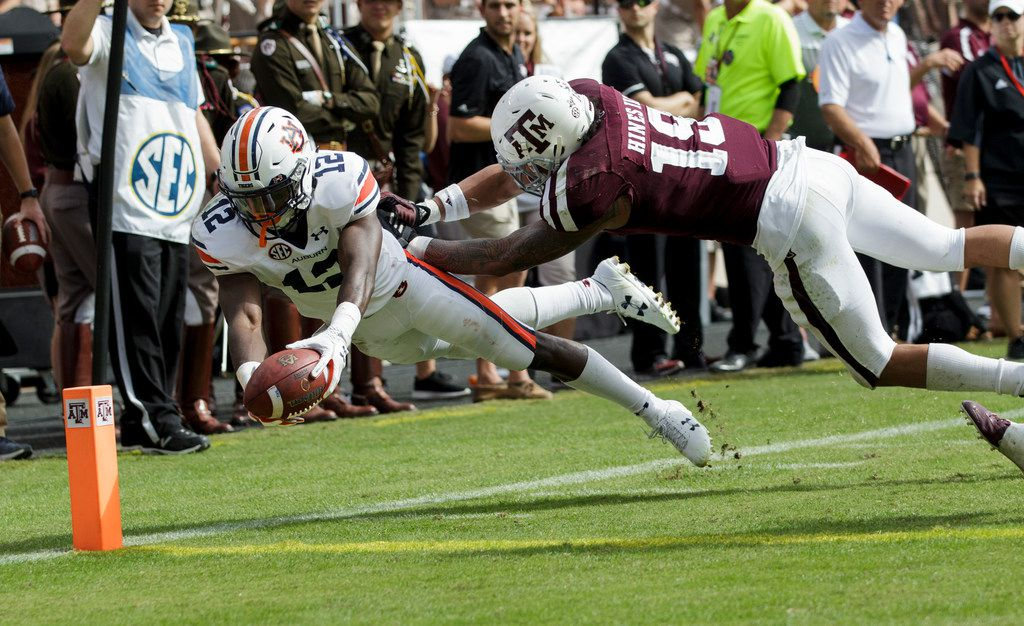 Auburn wide receiver Eli Stove (12) dives for the end zone for a touchdown as Texas A&M linebacker Anthony Hines III (19) defends during the second half of an NCAA college football game on Saturday, Nov. 4, 2017, in College Station, Texas. (AP Photo/Sam Craft)