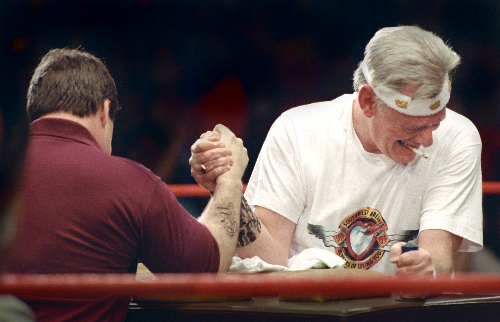 """Former Southwest Airlines CEO Herb Kelleher arm wrestles Kurt Herwald, CEO of Stevens Aviation Inc., at the Malice in Dallas at the Sportatorium on March 20, 1992, for the rights to the slogan """"Plane Smart."""" Kelleher won the match, although it was unclear whether the outcome was predetermined."""