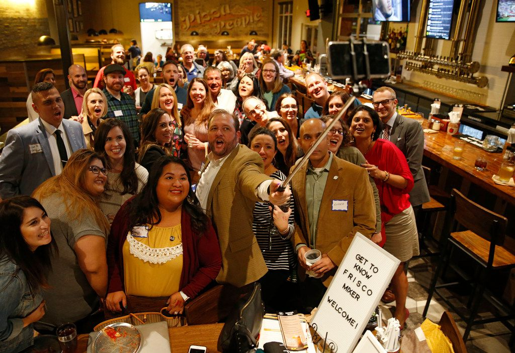 Darin Newbold takes a group photo with people at a Get to Know Frisco mixer at Rotolo's Craft & Crust in Frisco.