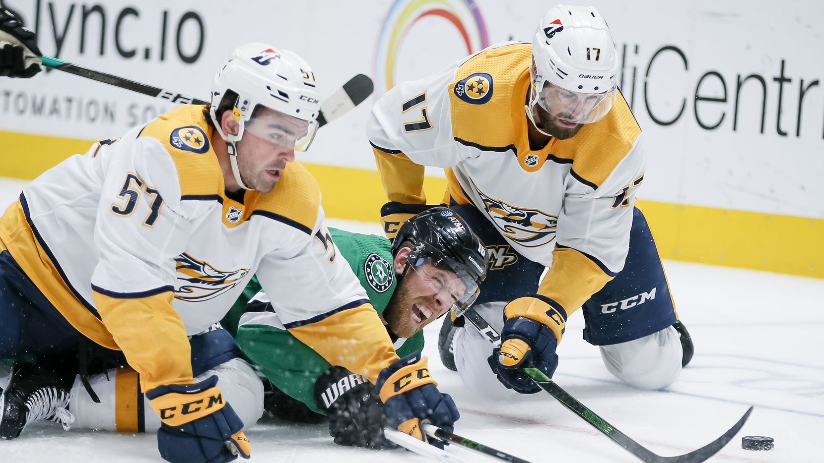 Dallas Stars forward Joe Pavelski (16) is checked to the ice by Nashville Predators defensemen Dante Fabbro (57) and Ben Harpur (17) during the third period of an NHL hockey game in Dallas Sunday, March 21, 2021.