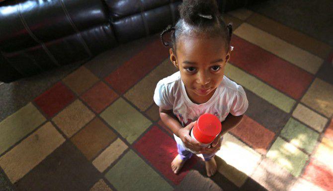 Reghan Ross, de 2 años, se para sobre un tapete que colocaron para proteger sus pies de la alfombra sucia en la casa de su madre, la cual renta de la familia Topletz.  (LOUIS DeLUCA/DMN)