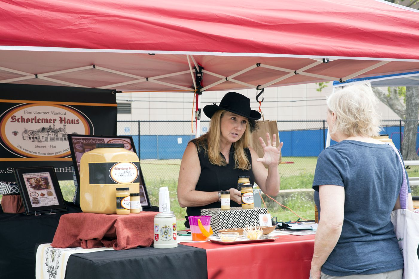 Vendor Lee Anne Schorlemar Sugg of Schorlemer Haus, a gourmet mustard company, speaks with a customer during the opening day of Saint Michael's Farmers Market.