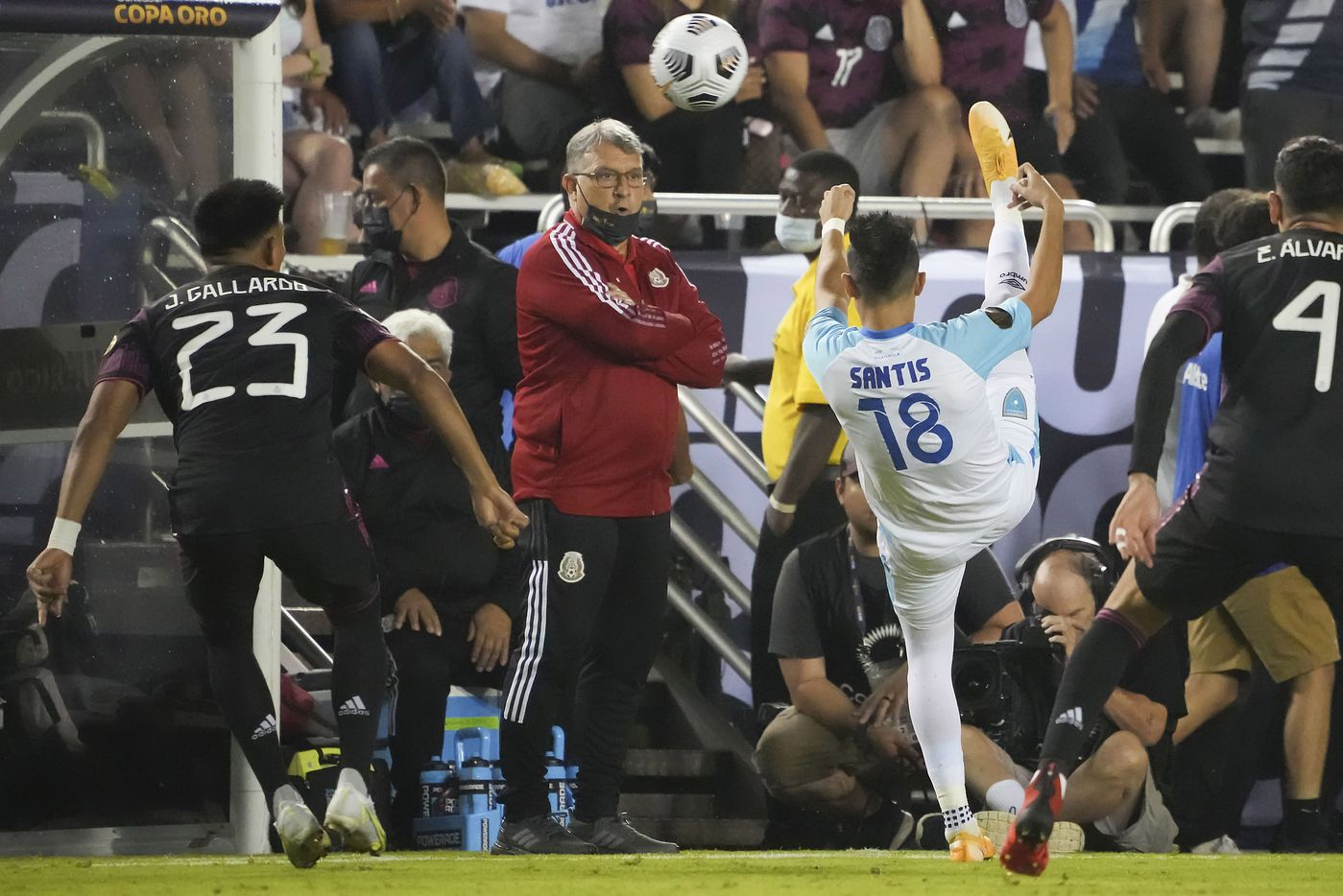 """Guatemala midfielder Oscar Santis (18) controls the ball in front of Mexico head coach Gerardo """"Tata"""" Martino  and midfielder Jesús Gallardo (23) during the first half of a CONCACAF Gold Cup Group A soccer match at the Cotton Bowl on Wednesday, July 14, 2021, in Dallas."""