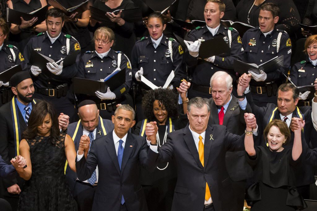 First Lady Michelle Obama, President Barack Obama, Mayor Mike Rawlings and his wife, Micki, joined hands at Tuesday's memorial service at the Morton H. Meyerson Symphony Center.