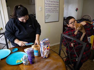 Rosa Mendoza and son David Sanroman, 7, smile as the power comes back on while she was preparing him a peanut butter and jelly sandwich following a power outage at their Piedmont Addition apartment in Dallas on Wednesday, Feb. 17, 2021. Mendoza's pipes burst Tuesday and hasn't had consistent power. (Juan Figueroa/ The Dallas Morning News)