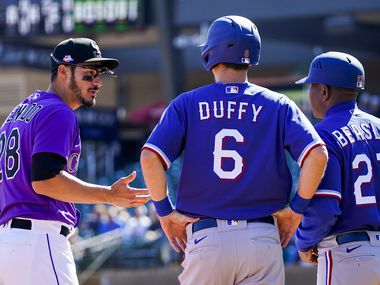 Rockies third baseman Nolan Arenado chats with Rangers infielder Matt Duffy (6) and third base coach Tony Beasley (27) during the second inning of a spring training game at Salt River Fields at Talking Stick on Wednesday, Feb. 26, 2020, in Scottsdale, Ariz.