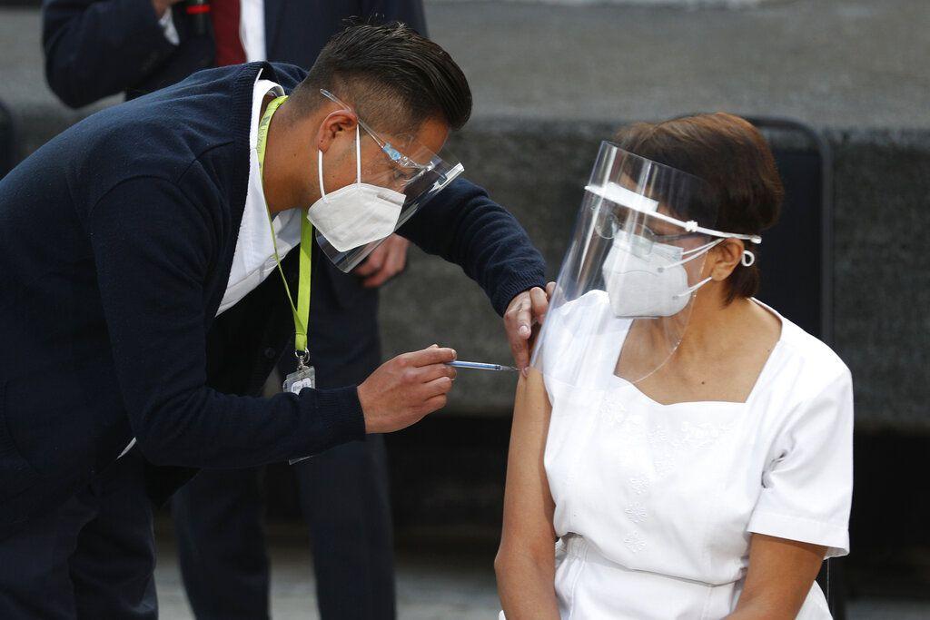La trabajadora de salud María Ramírez es la primera en vacunarse contra COVID-19 en el Hospital General de la Ciudad de México, el jueves 24 de diciembre de 2020 en la madrugada. Los primeros lotes de vacunas producidas por Pfizer y su socio alemán, BioNTech llegaron el día anterior.