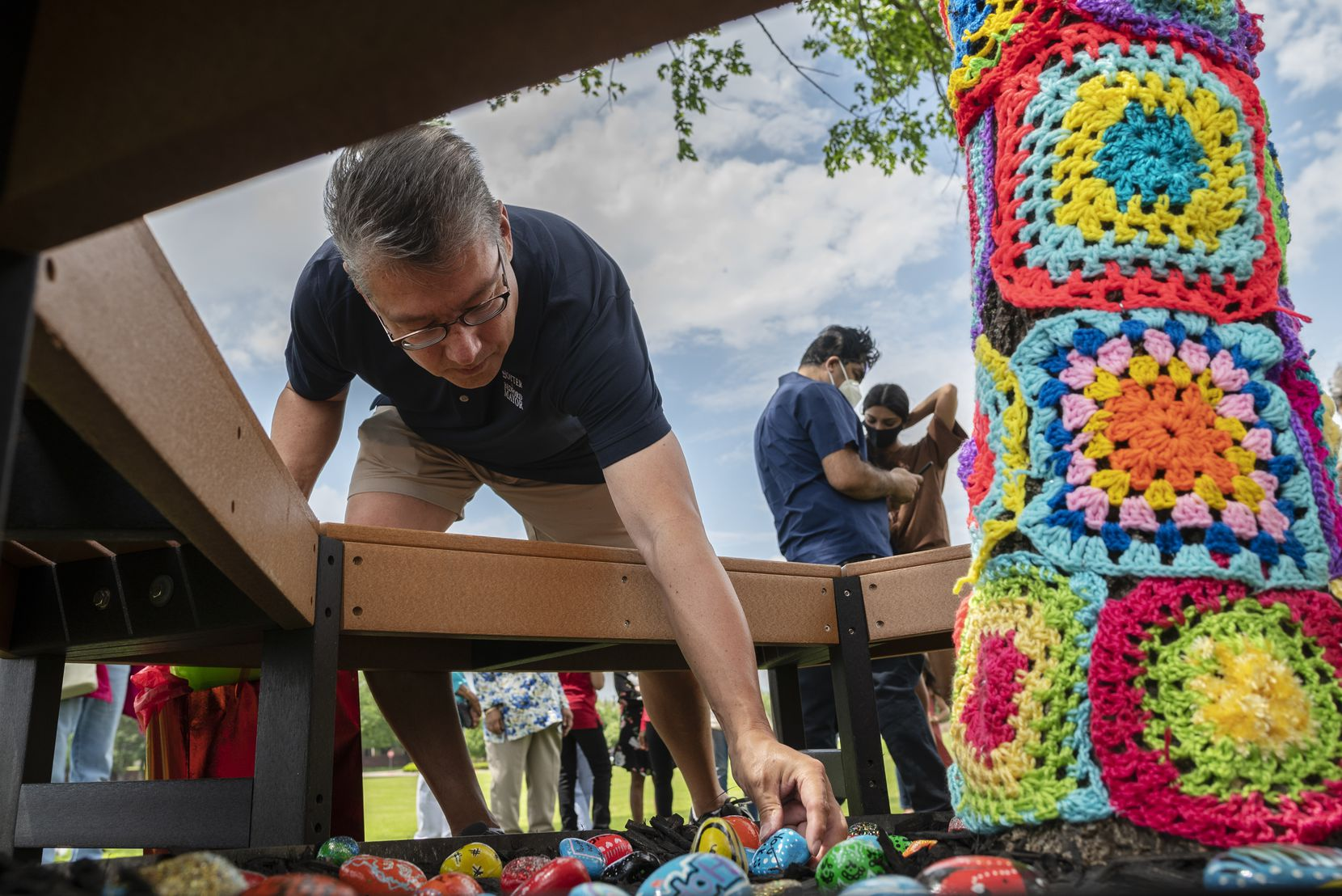 Bedford Mayor Michael Boyter places a painted rock with a positive message written on it at the base of Anya Ali's Girl Scout project outside of the Bedford Public Library.