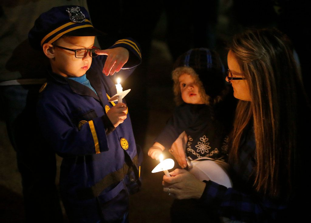 Kristen Garza (right) with her 7-month-old daughter Ally Garza (center) and 4-year-old son AJ Garza, dressed as a police officer, honored Det. Jerry Walker at Wednesday night's vigil.  (Jae S. Lee/The Dallas Morning News)