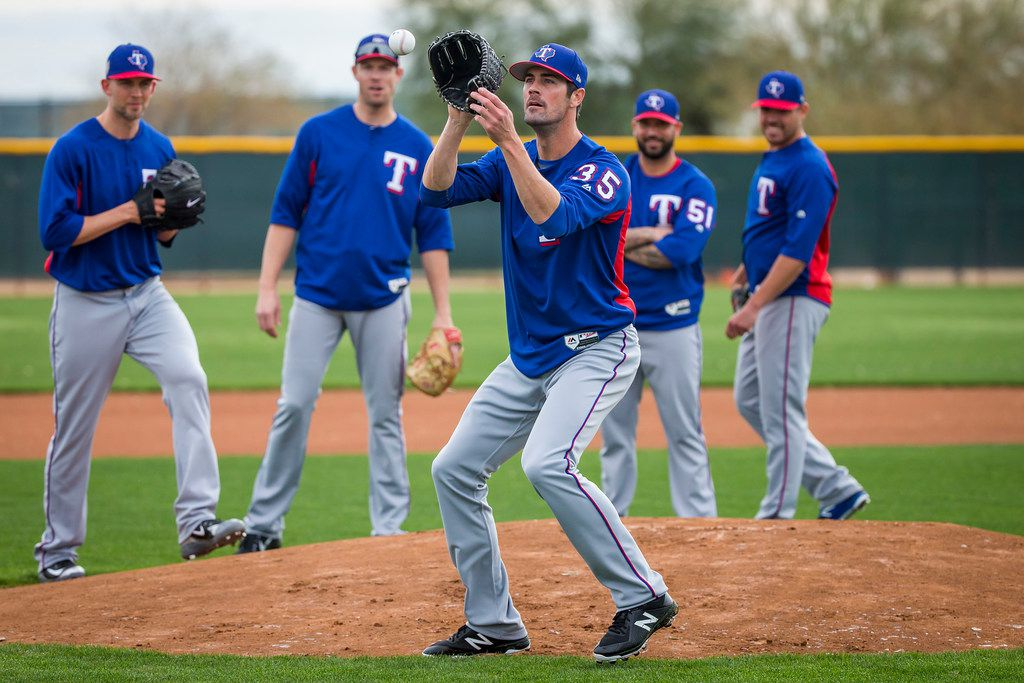 Texas Rangers starting pitcher Cole Hamels participates in a fielding drill during a spring training workout at the team's training facility on Friday, Feb. 16, 2018, in Surprise, Ariz. In the background, from left, are Mike Minor, Doug Fister, Matt Bush and Matt Moore.  (Smiley N. Pool/The Dallas Morning News)